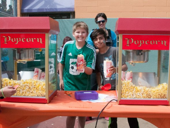 Two boys serving popcorn at an outdoor school festival