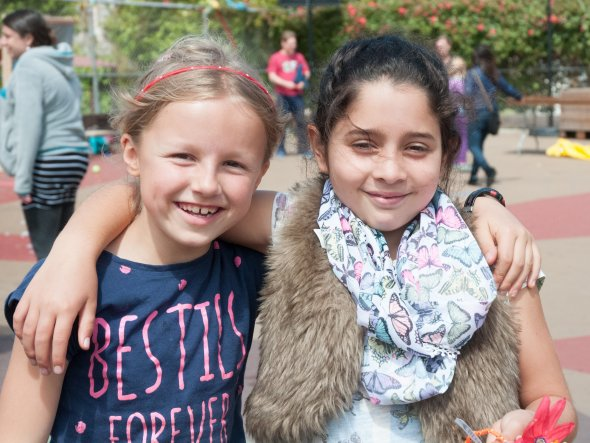 Two girls stand arm in arm at an outdoor school festival