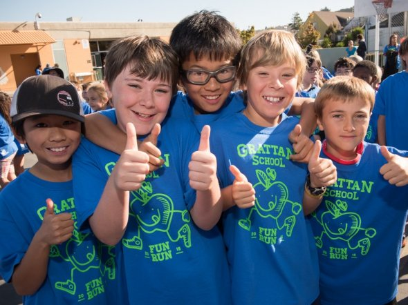 Five boys giving their thumbs up at an outdoor school fitness event