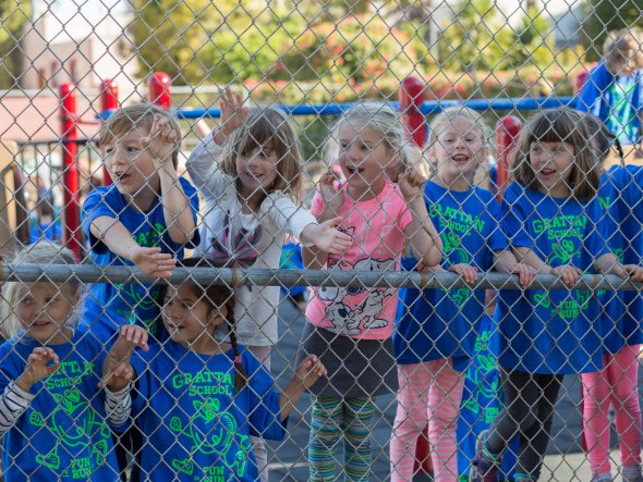 Children cheering each other on at an outdoor school fitness event