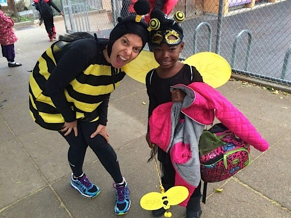 Parent and girl dressed up as bumblebees at a school Halloween event