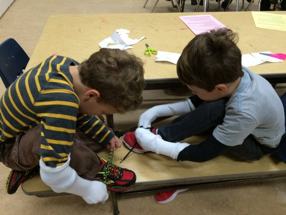 Boys with socks on their hands try to tie their shoes at a school inclusion awareness event