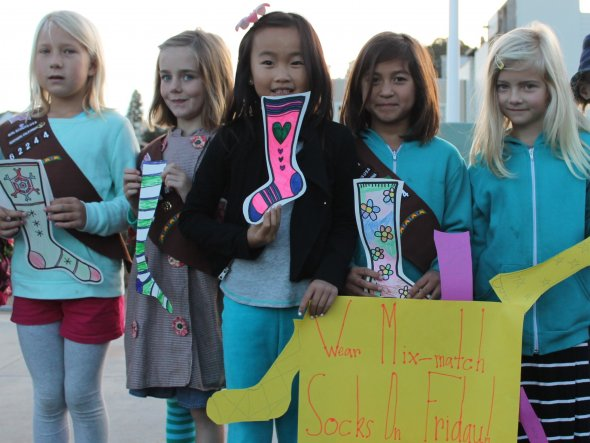 Five girls hold up handmade sock drawings to announce a school anti-bullying event