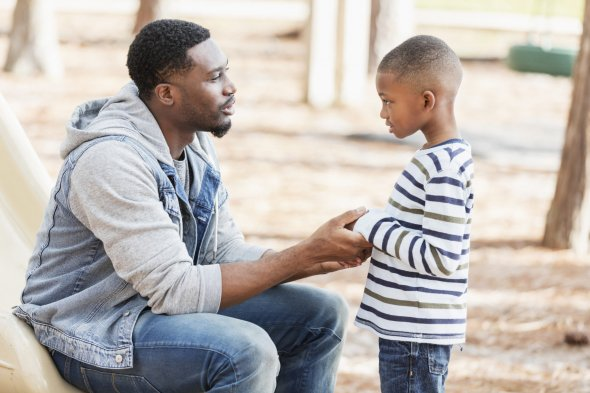 African american dad talking to young son