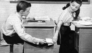 Black and white old time photo showing kids passing notes in class