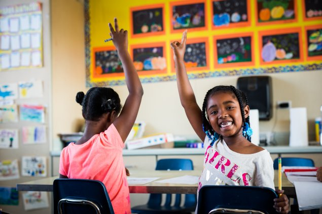 Two elementary school students raising their hands