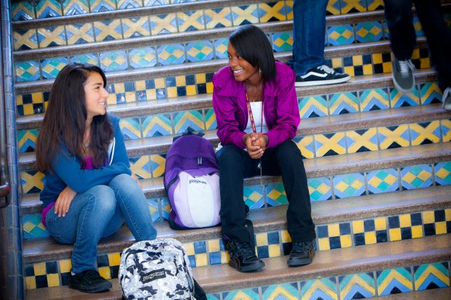 High school students sitting on colorful tiled stairs