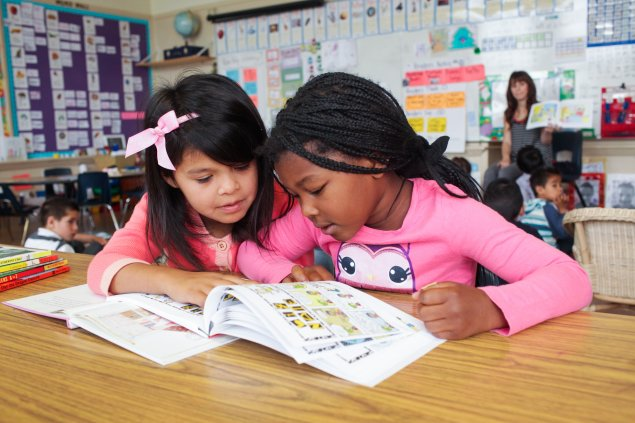Two elementary school students looking at a book together