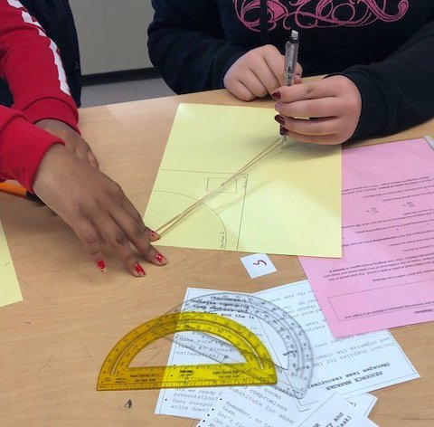 Hands of two students using a rubberband to enlarge an image. Protractor and geometry papers on the desk.