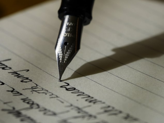 A pen writes on a paper.