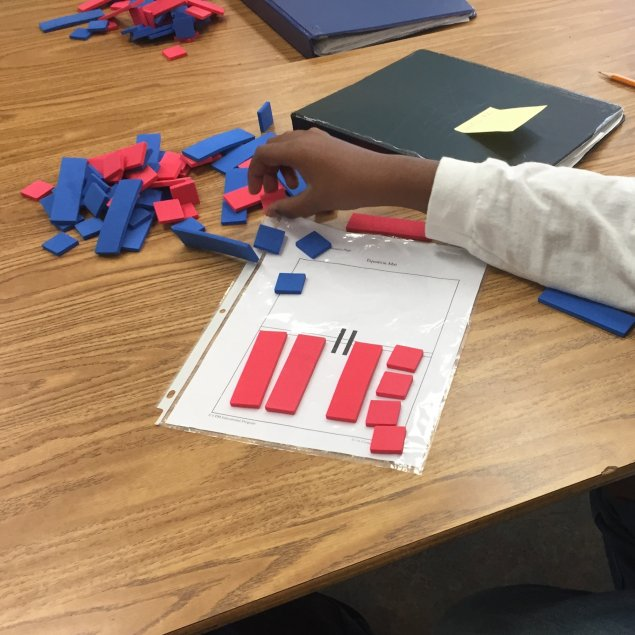 Student working with algebra tiles on equation mat