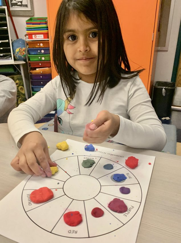 Child making color wheel with colored clay