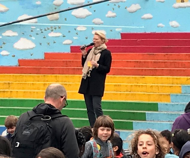 Woman standing on rainbow painted steps talking to group