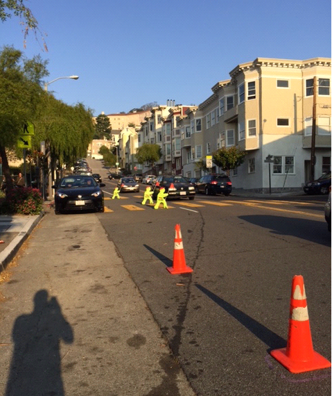 photo of traffic cones blocking lane of road near sidewalk