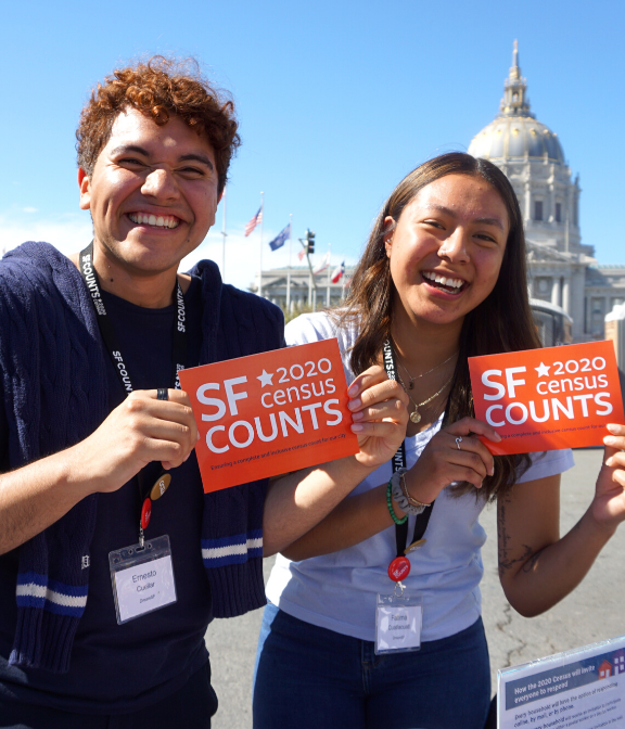 man and woman holding up SF Counts signs