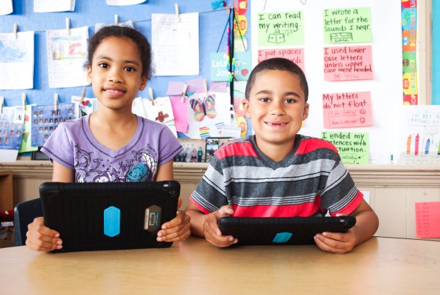 Two students holding iPads