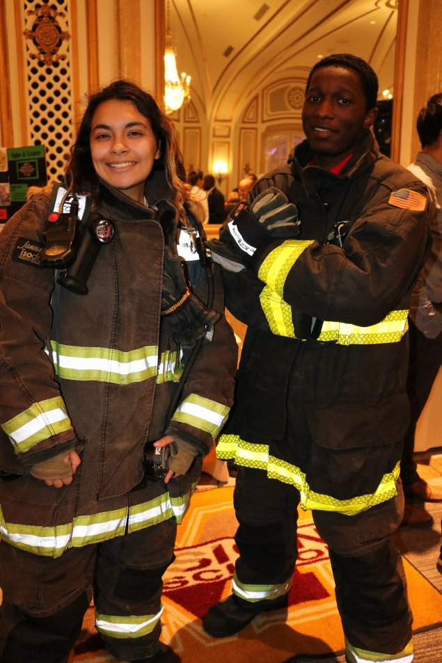 Two students try on firefighter gear as part of a career exploration event.