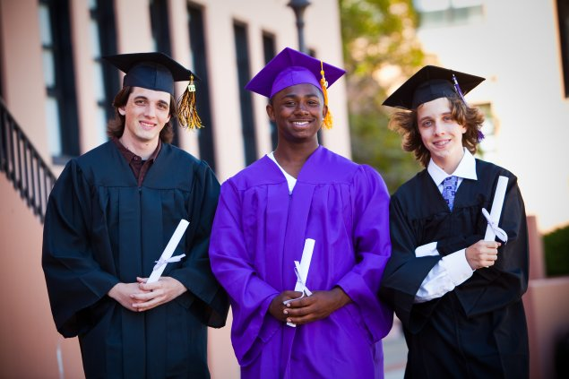 Three students with graduation gowns