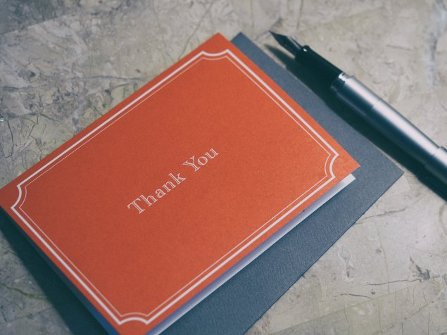 A fountain pen next to red thank you card.