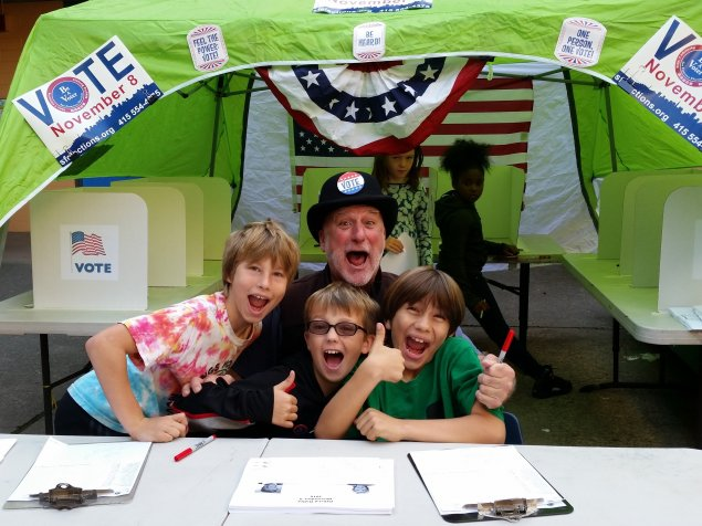 Students and a teacher manage a student voting booth at a school election day event