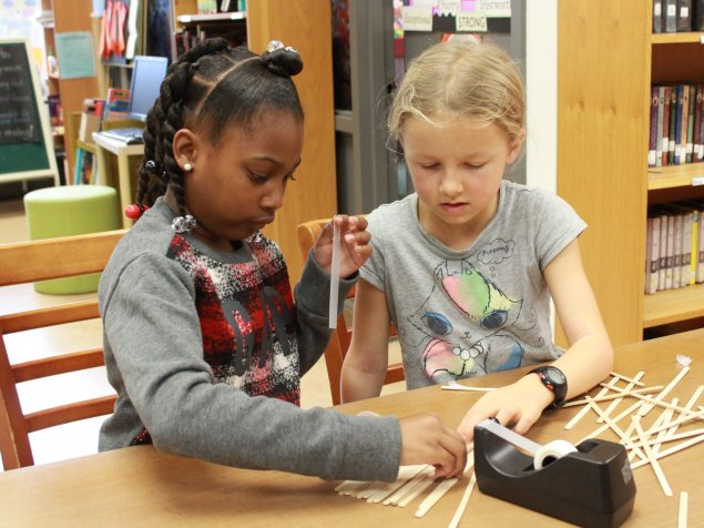 Two girls work together to build a structure at a school inclusion awareness event