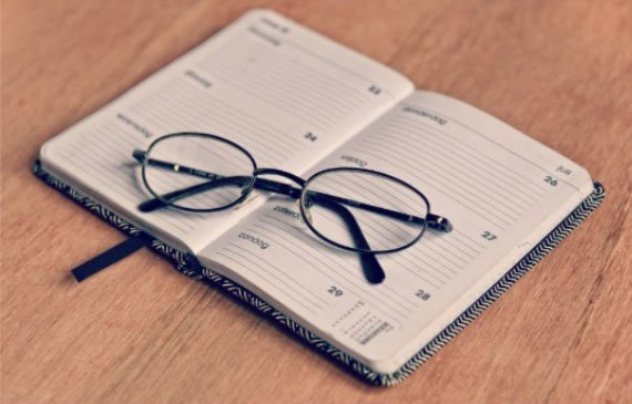 Planner with eyeglasses on top
