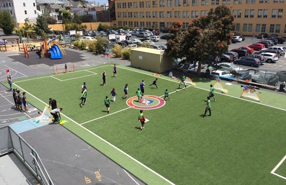 People playing soccer in a shared schoolyard